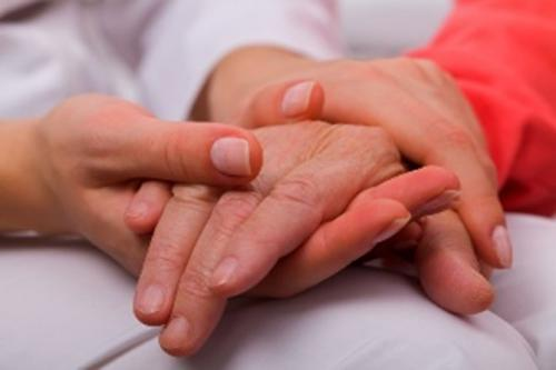 Carer comforting someone by holding their hand